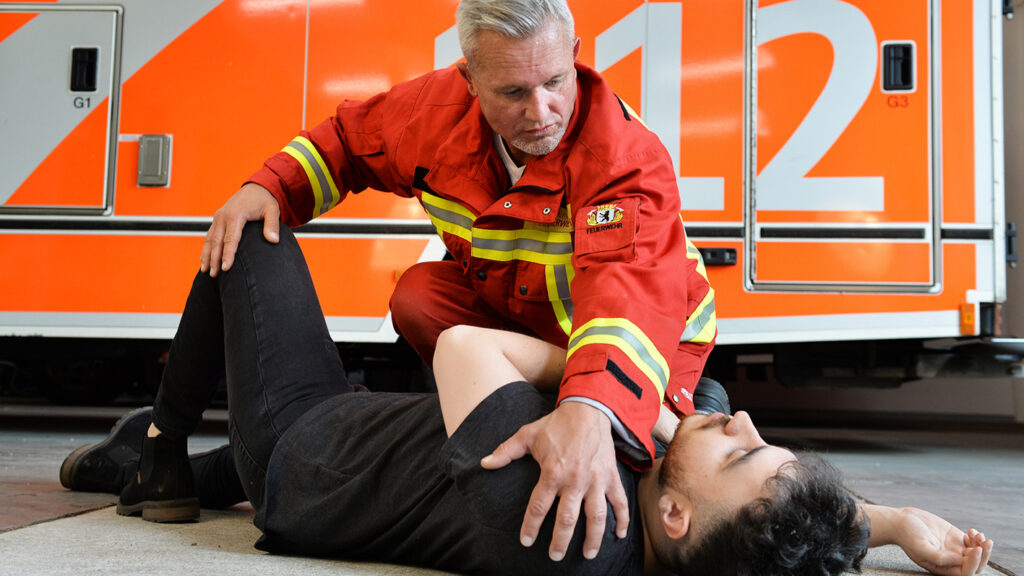 Ein Rettungssanitäter bringt eine Person in die stabile Seitenlage