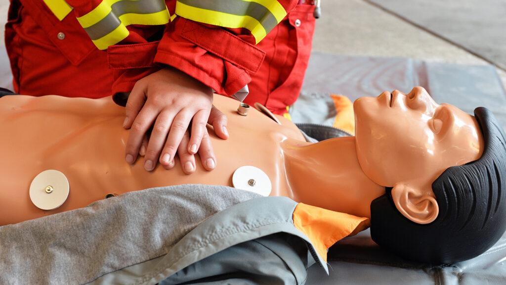 Eine Rettungssanitäterin demonstriert die Reanimation an einer Puppe