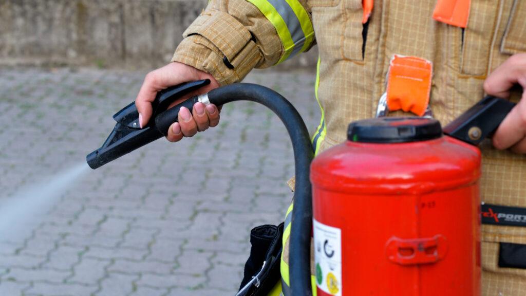 Eine Brandmeisterin der Feuerwehr demonstriert die Benutzung eines Feuerlöschers